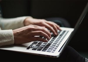 hands typing on a computer keyboard