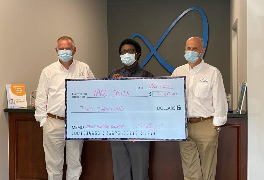 scholarship winner Nigel Smith smiling with Chuck Brown and David Brown and large check