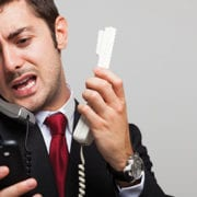 man frustrated trying to use multiple phones at once