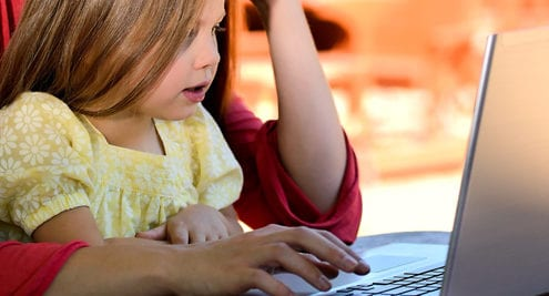 child on parents lap using laptop for cybersecurity awareness