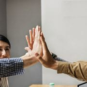 employees smiling and high-fiving to show engagement