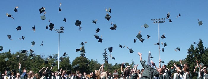 graduates throwing caps in the air in celebration of scholarship