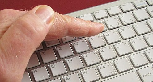hand covering keyboard for blog about 3 tips for stronger passwords you can actually remember
