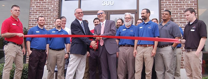 Chuck and David Brown with Infinity, Inc. staff cutting red ribbon