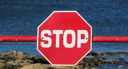 stop sign over the water