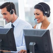 smiling professionals with headsets and computers