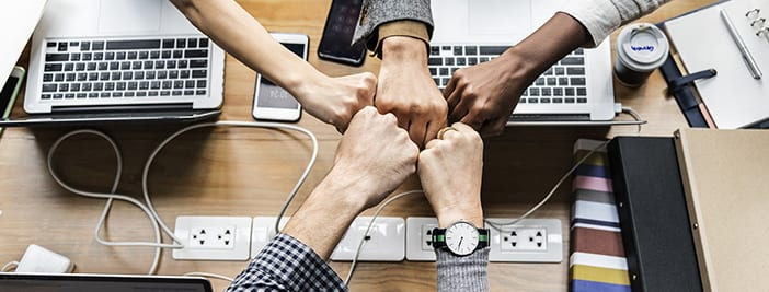 hands fistbumping over laptops for untapped power of teams