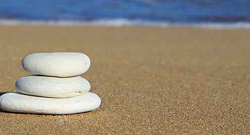 3 rocks balancing on a beach to show work life balance