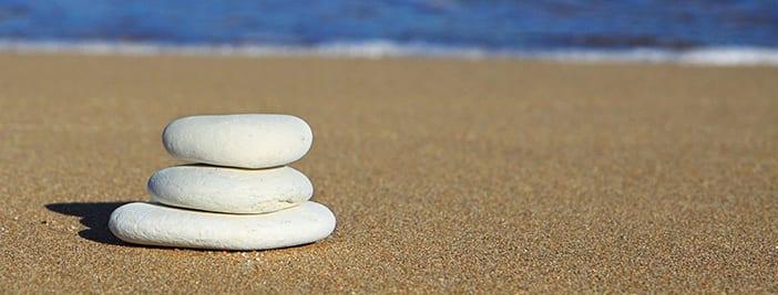 3 rocks balancing on a beach to show work life balance