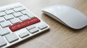 computer keyboard with red 'get me out of here' button for technology news scams