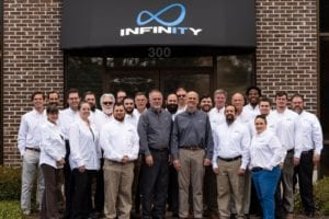 Infinity Inc staff smiling in front of Savannah IT office