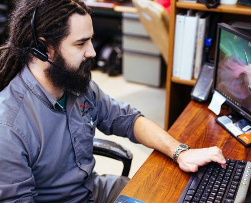 man wearing headset typing at computer