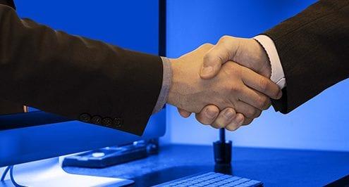 handshake through computer welcoming new team members